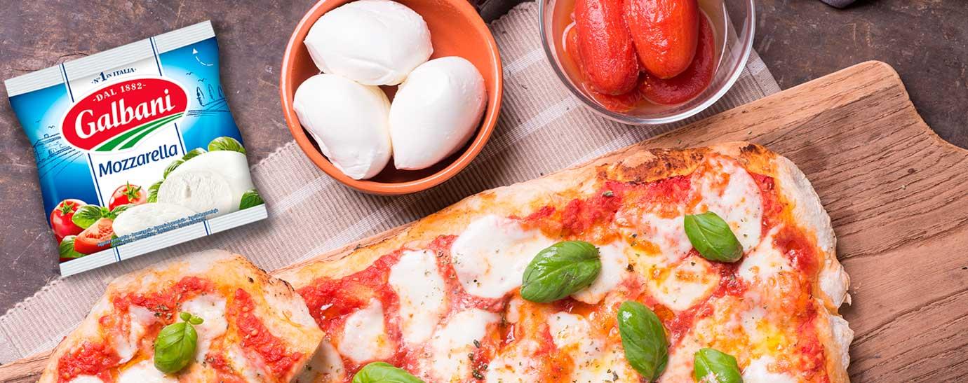 una foccacia con dos cuencos al lado uno de mozarella Galbani y otro de tomate