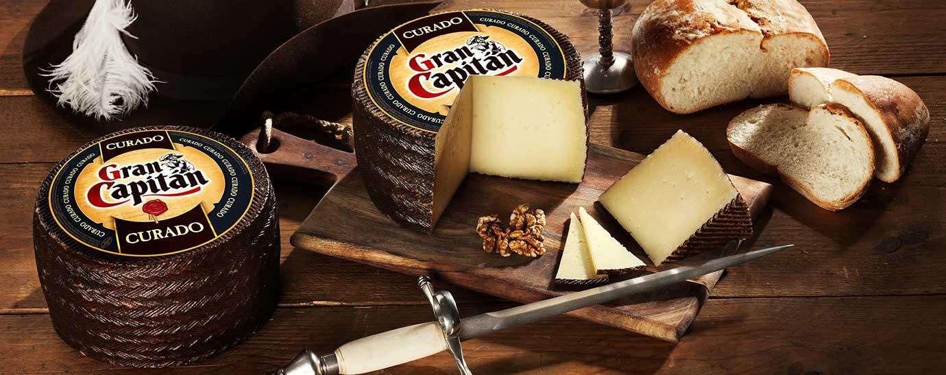 Queso Gran Capitán Curado con un cuarto cortado sobre una tabla, con frutos secos y un cuchillo al lado