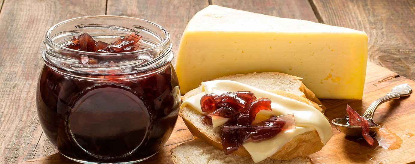 Tosta de queso con mermelada y bote de mermelada con cuña de queso