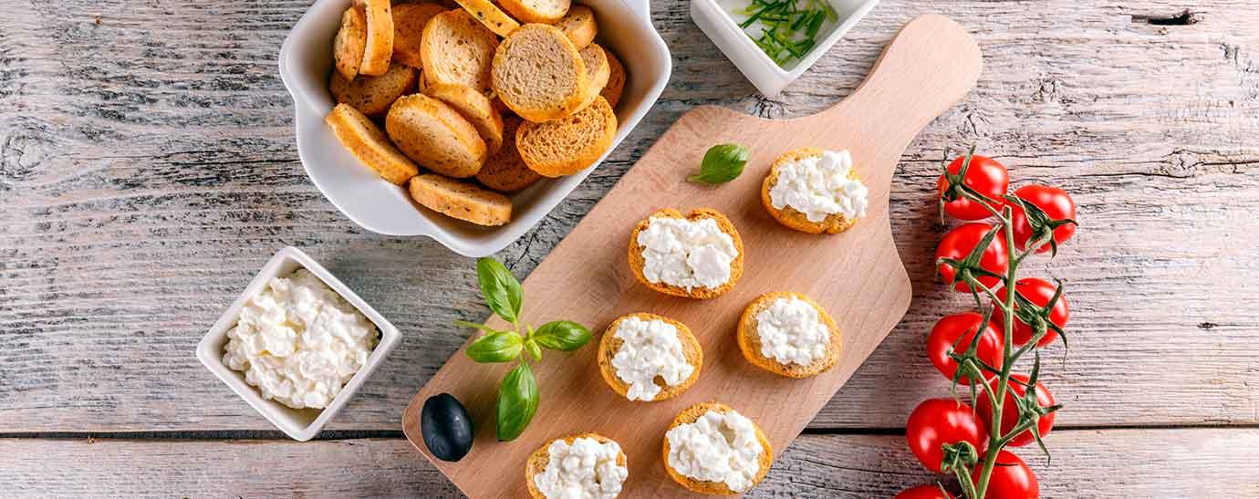 Tabla con queso de untar, pan y tomates
