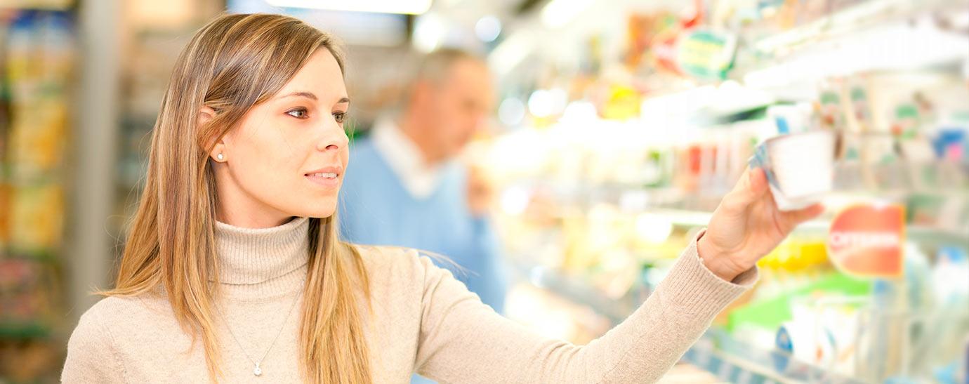 Mujer escogiendo un queso fresco en el supermercado