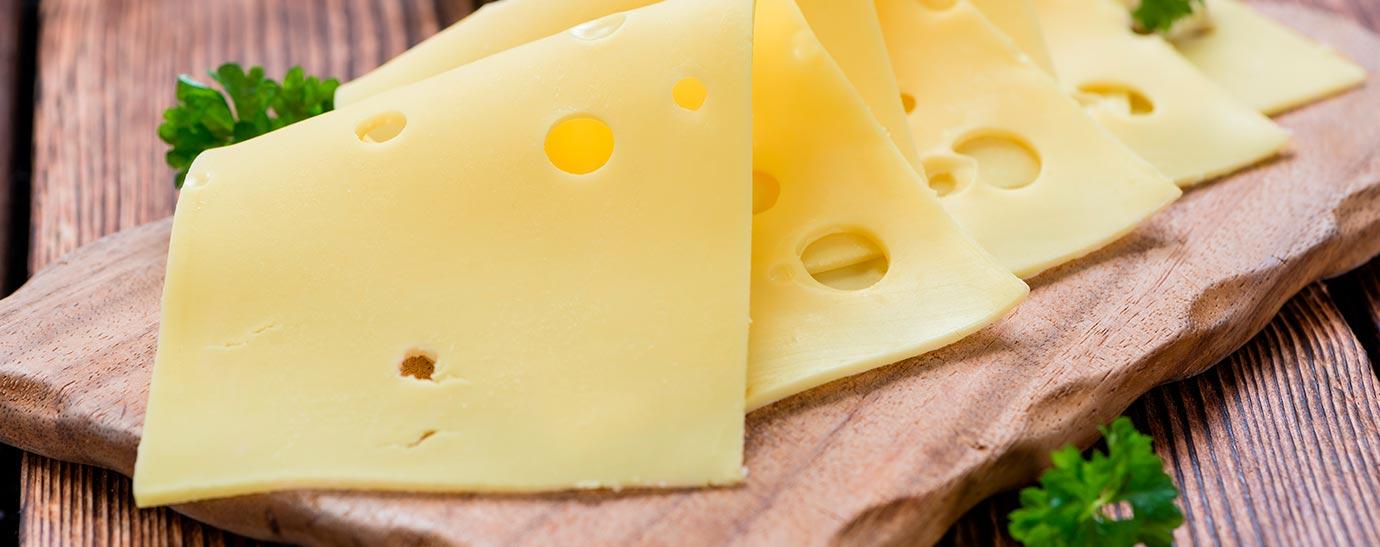 Cuatro lonchas de queso emmental sobre una tabla