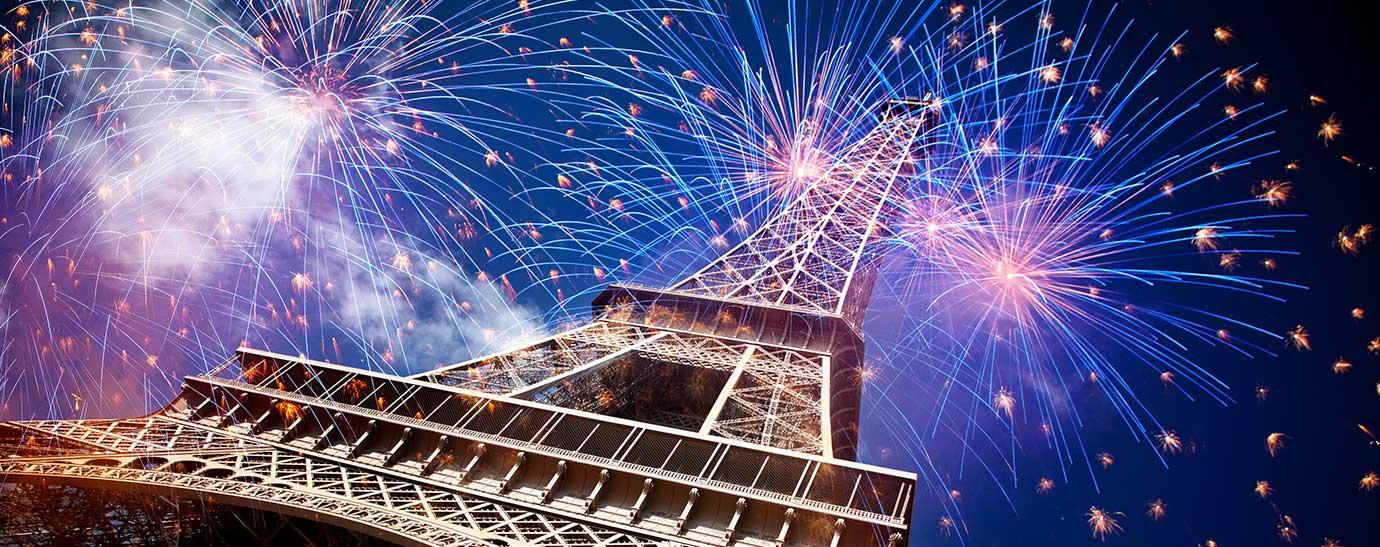 La Torre Eiffel por la noche iluminada con fuegos artificiales
