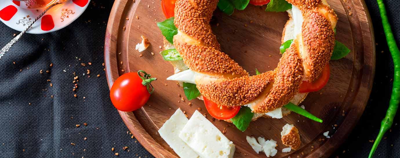 Bagel de queso tierno, espinacas y tomate sobre tabla redonda de madera.