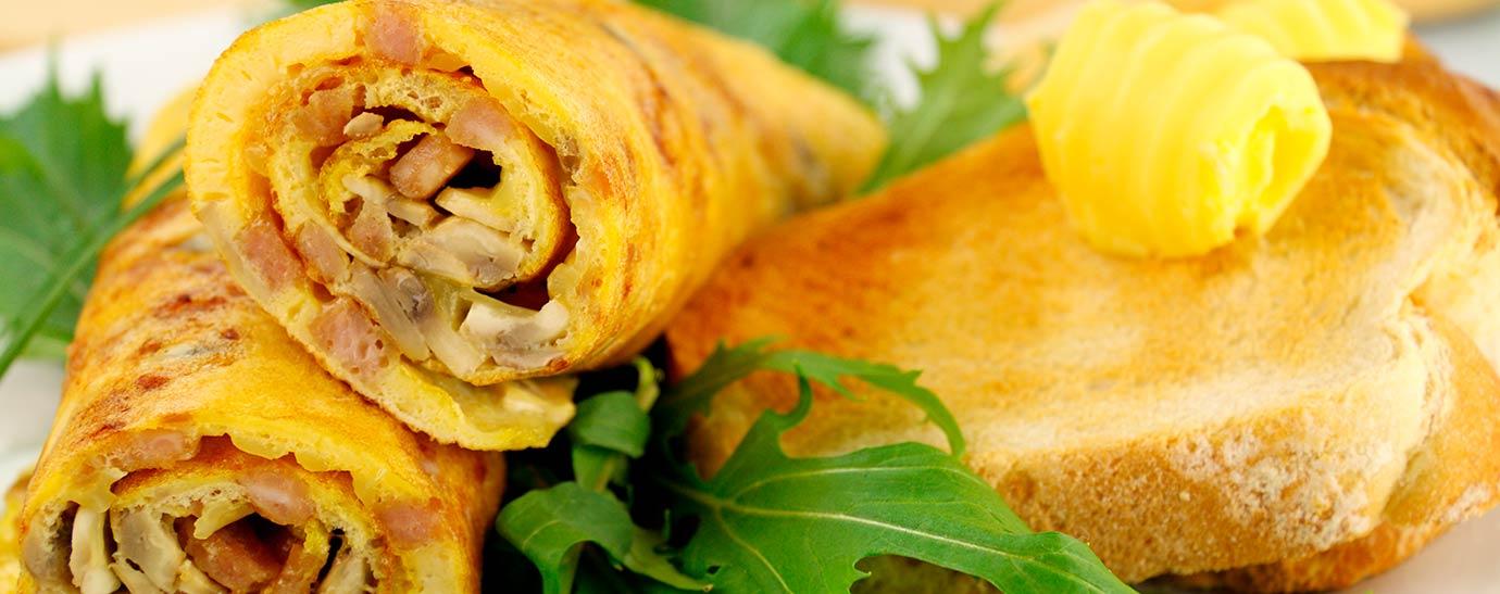 Tortilla rellena de queso tierno y champiñones y enrollada sobre un plato blanco decorado con cebollino.