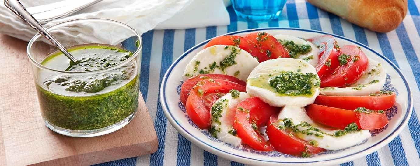 Plato de ensalada caprese con pesto sobre mantel de rayas azules