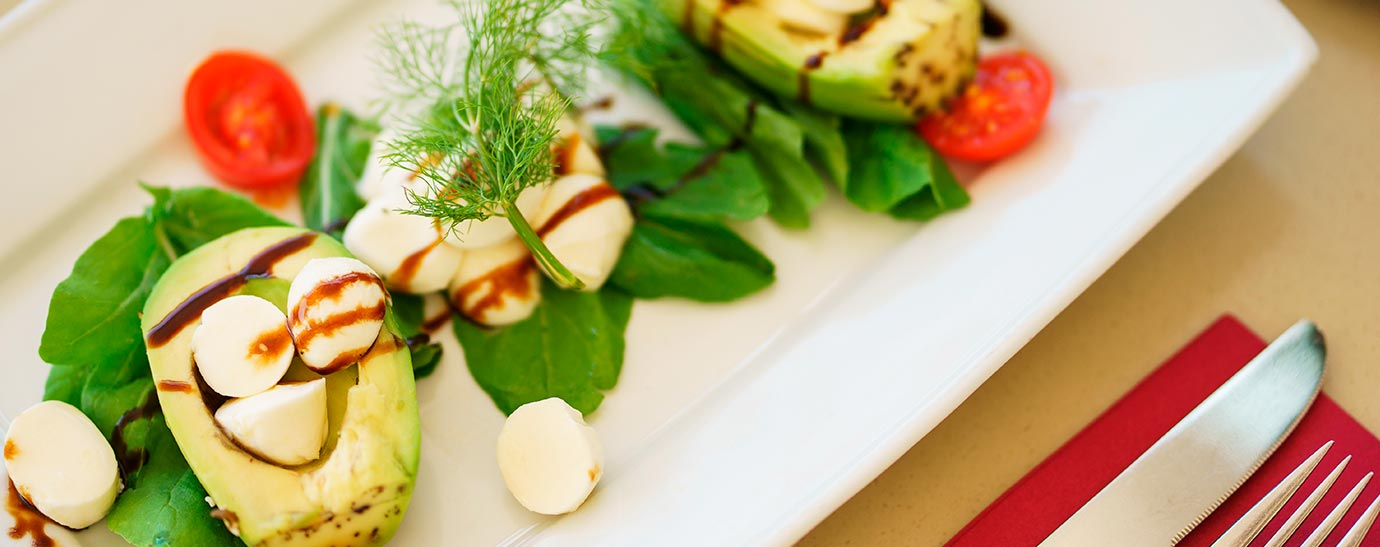 Varios aperitivos de tomate, aguacate y queso en plato