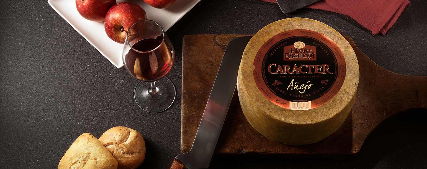 Queso redondo en tabla, con cuchillo, copa de vino, manzanas y pan