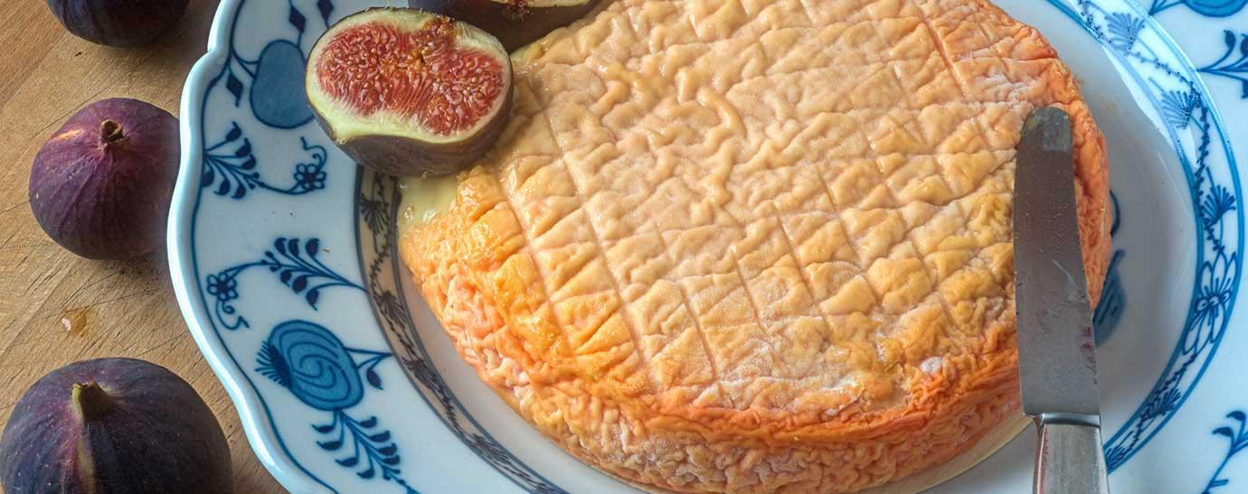 Queso Époisses sobre plato decorado, acompañado de higos frescos