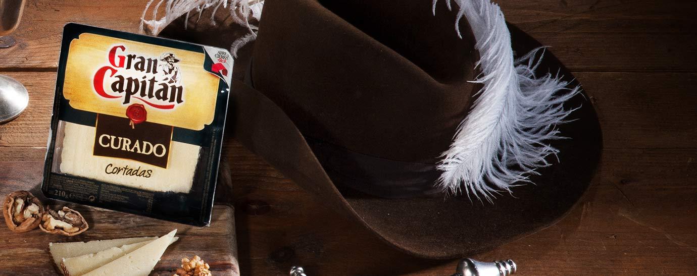 queso Gran Capitán Curado sobre tabla de madera junto con un sombrero con una pluma
